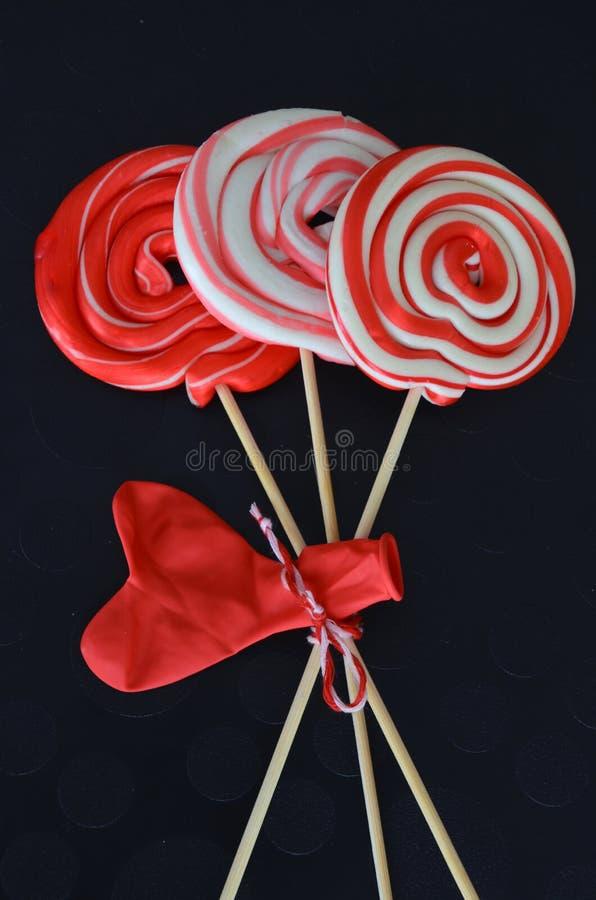 Caramelle dolci rosse con il pallone del cuore Giorno felice del ` s del biglietto di S. Valentino con fondo nero immagine stock