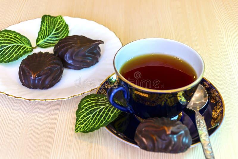 Caramelle gommosa e molle del cioccolato e una tazza di tè nero fotografia stock