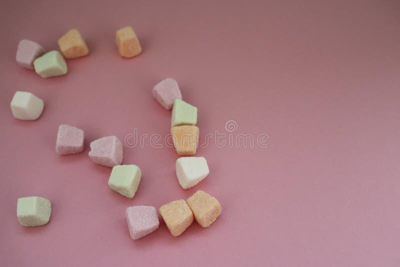 Caramelle gommosa e molle variopinte su fondo rosa fotografia stock