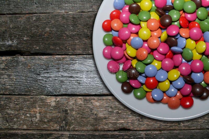 Caramelle variopinte del cioccolato zuccherato sul piatto immagine stock libera da diritti