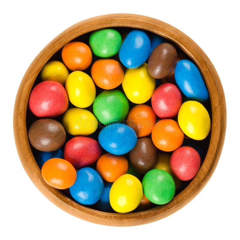 Caramelle variopinte dell'arachide del cioccolato in ciotola di legno sopra bianco fotografie stock libere da diritti