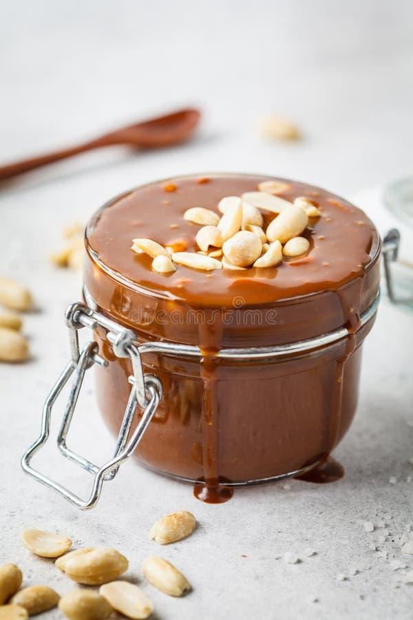 Caramello salato casalingo con i dadi in barattolo di vetro, spazio della copia Ingrediente per le risatine del dolce immagine stock