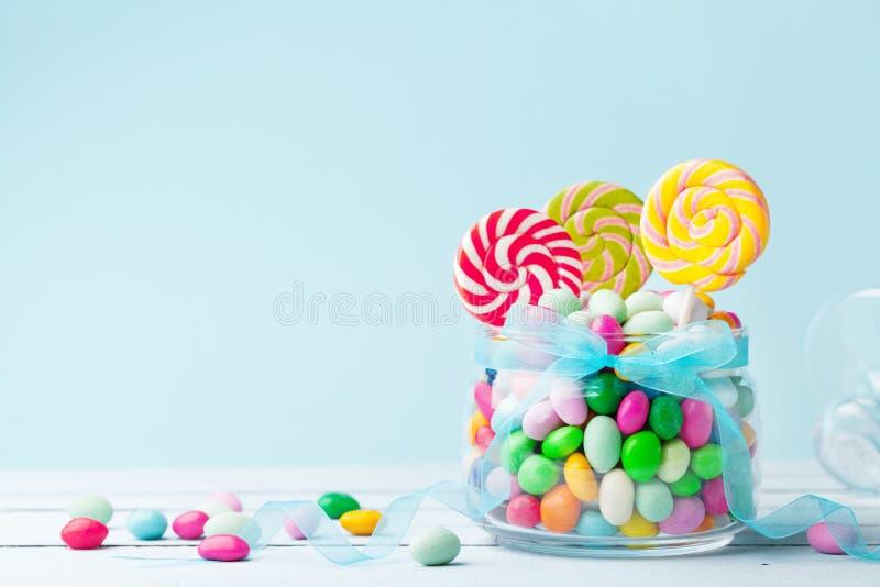 Caramelo colorido dulce en el tarro adornado con la cinta del arco contra fondo azul Regalos para la fiesta de cumpleaños foto de archivo libre de regalías