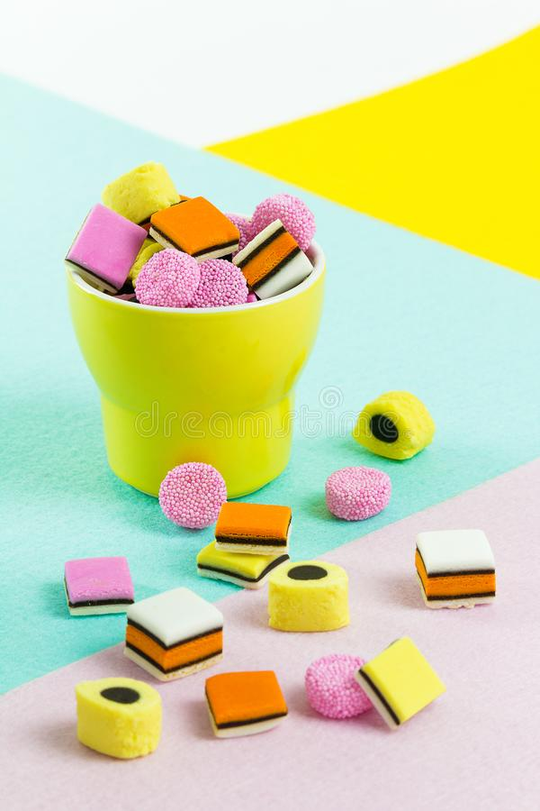 Caramelo de la comida de la moda: regaliz allsorts en una taza amarilla foto de archivo