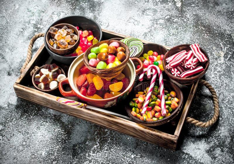caramelo de los dulces, frutas escarchadas con la melcocha y jalea en una bandeja de madera fotos de archivo libres de regalías
