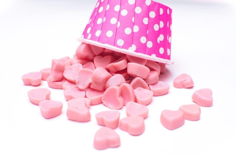 Caramelo del corazón que cae en las tazas de papel del lunar rosado aisladas foto de archivo