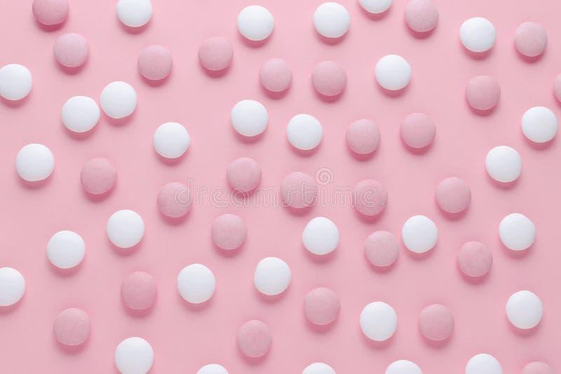 Caramelo del rosa y blanco o píldoras en el fondo del color en colores pastel, modelo abstracto imagen de archivo