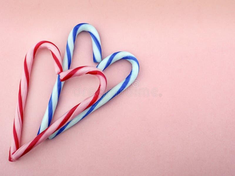 Caramelo en blanco y rosado y en las rayas blancas y azules dobladas en la forma de corazones en un fondo rosado foto de archivo