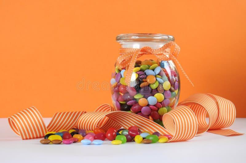 Caramelo en el tarro de cristal en fondo anaranjado y blanco fotografía de archivo