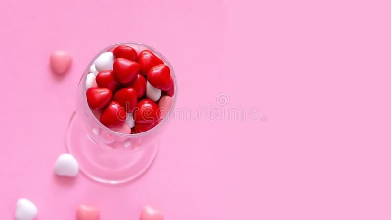 Caramelo o píldoras multicolor en la forma de corazones en copa de vino El día de tarjeta del día de San Valentín del concepto o  foto de archivo