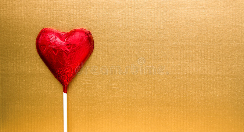 Caramelo rojo del corazón en el oro fotos de archivo libres de regalías