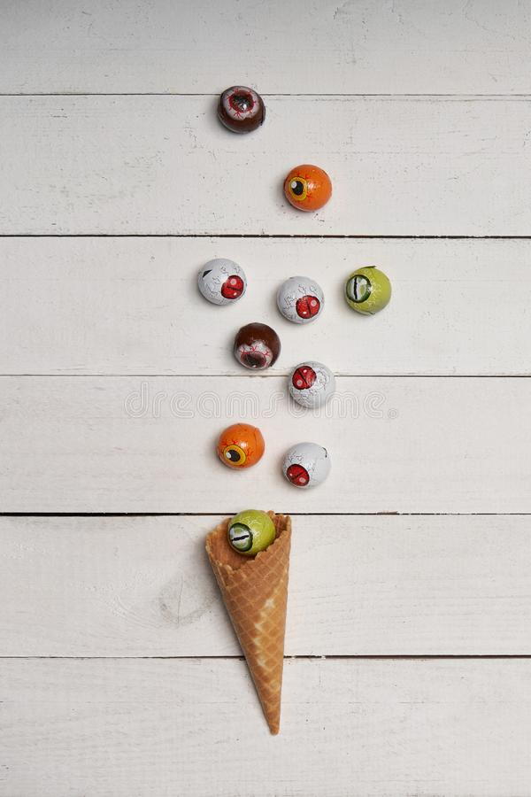 Caramelos asustadizos del ojo con el cono de la galleta sobre los tablones de madera blancos imagen de archivo libre de regalías