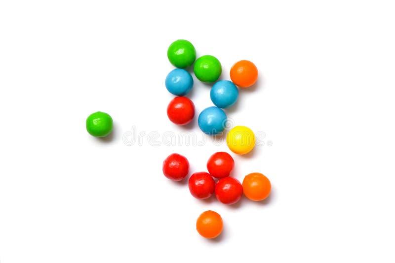 Caramelos coloreados - coloridos del pequeño caramelo de chocolates en el fondo blanco, visión superior imagen de archivo libre de regalías