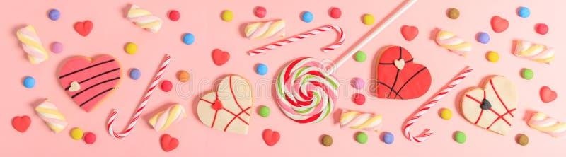 Caramelos coloridos en el fondo rosado, visión superior imagenes de archivo
