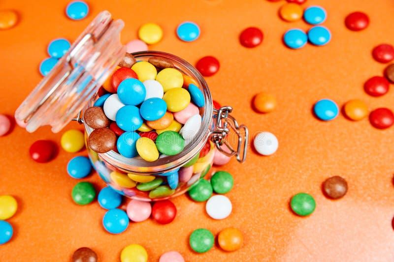 Caramelos coloridos en el tarro de cristal en fondo rojo de las naranjas imagen de archivo
