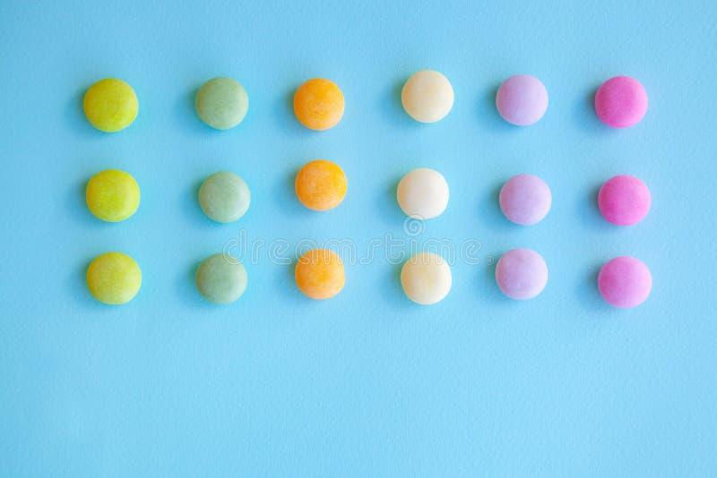 Caramelos coloridos en fondo azul imagen de archivo