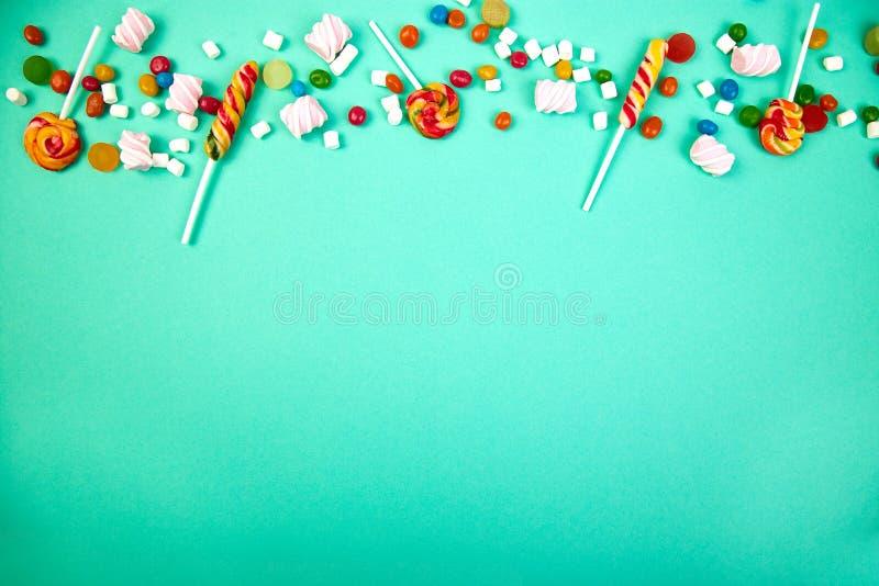 Caramelos coloridos en fondo en colores pastel de la turquesa Endecha plana imagenes de archivo