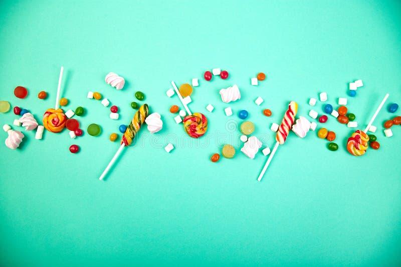 Caramelos coloridos en fondo en colores pastel de la turquesa Endecha plana imagen de archivo