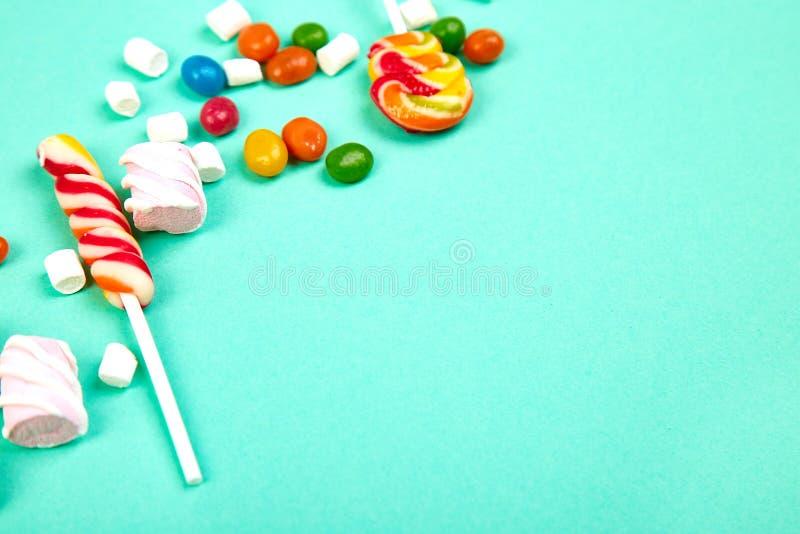 Caramelos coloridos en fondo en colores pastel de la turquesa Endecha plana fotografía de archivo