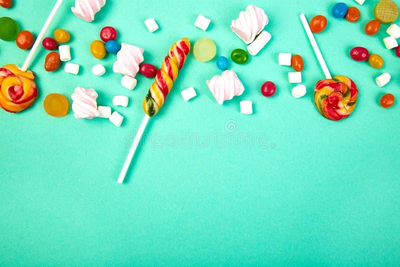 Caramelos coloridos en fondo en colores pastel de la turquesa Endecha plana foto de archivo libre de regalías