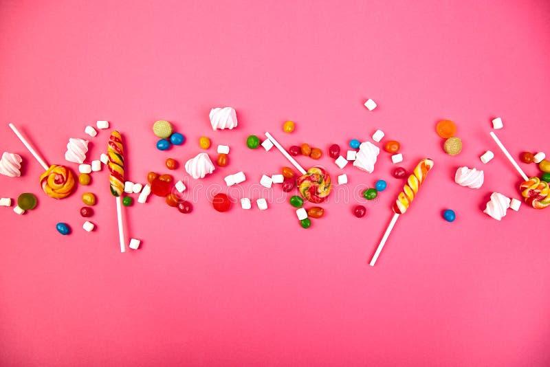 Caramelos coloridos en fondo rosado Endecha plana fotos de archivo