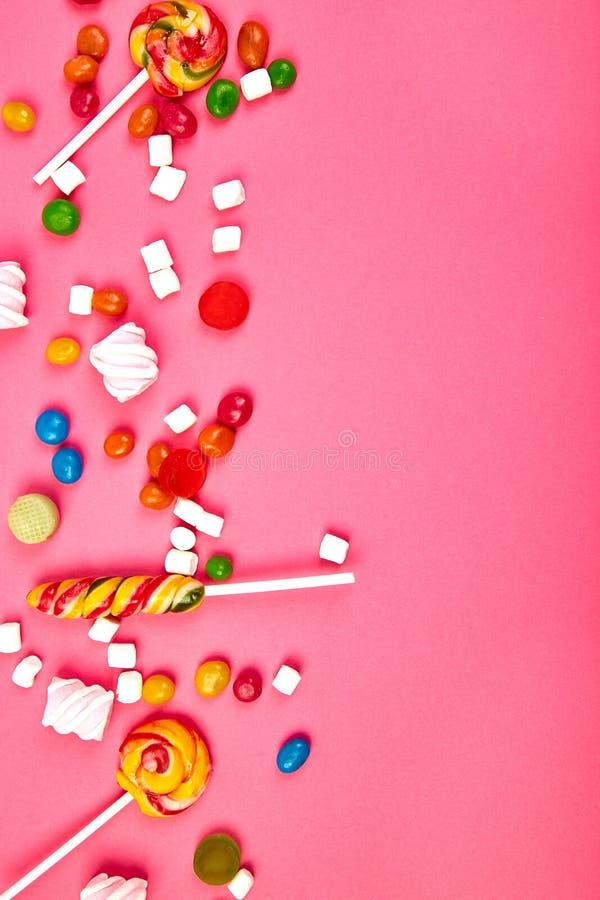 Caramelos coloridos en fondo rosado Endecha plana imagen de archivo