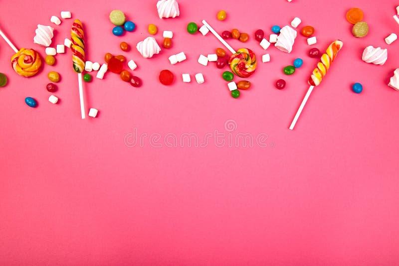 Caramelos coloridos en fondo rosado Endecha plana fotografía de archivo