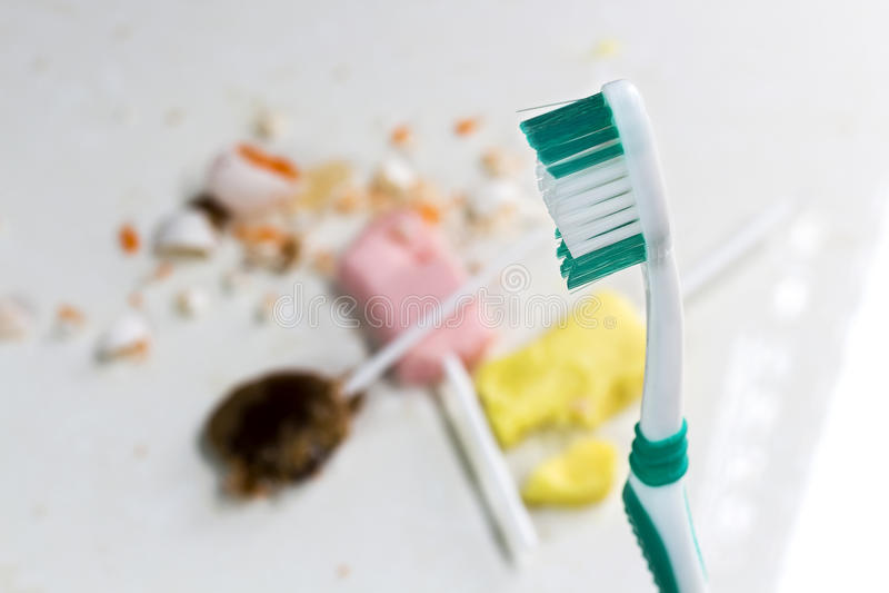 Caramelos con el azúcar y el cepillo de dientes en fondo gris fotografía de archivo libre de regalías