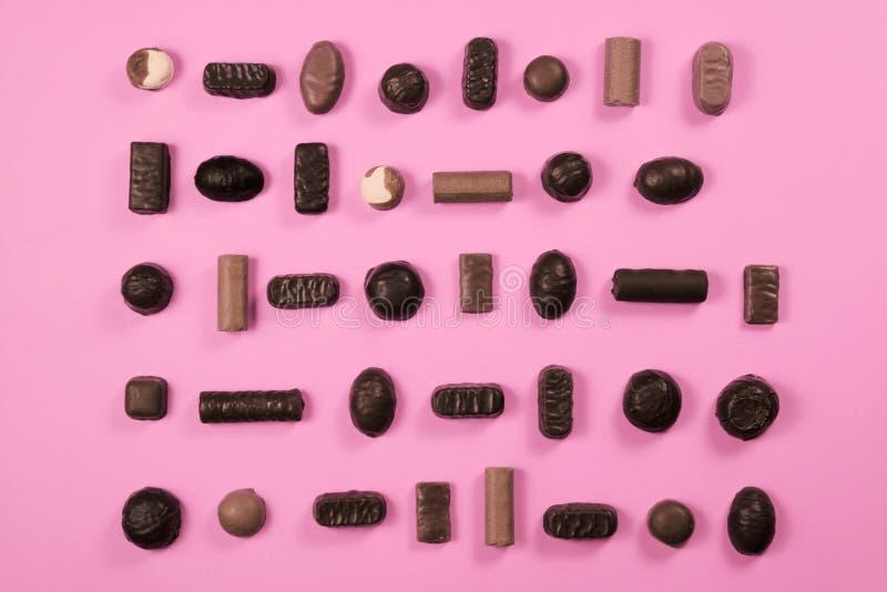 Caramelos de chocolate aislados en fondo rosado foto de archivo