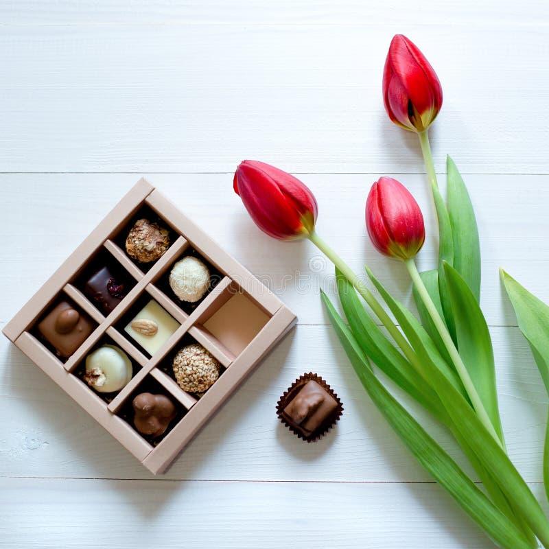 Caramelos de chocolate en la caja Caja y tulipanes del caramelo para el regalo romántico en el fondo blanco fotografía de archivo