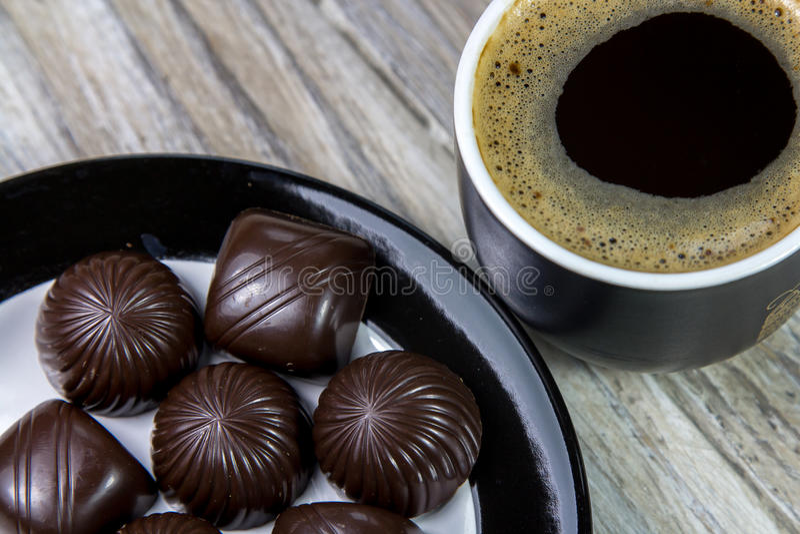Caramelos de chocolate en una placa y una taza de café en una superficie de madera fotografía de archivo