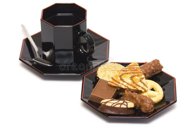 Caramelos de chocolate y taza de té imagen de archivo libre de regalías