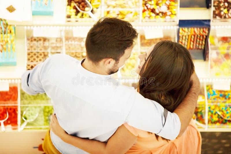 Caramelos de compra de los pares jovenes fotos de archivo
