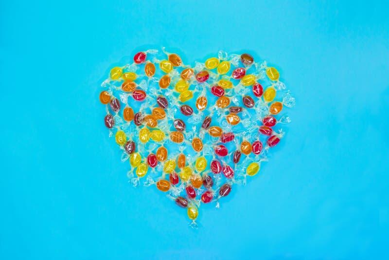 Caramelos en forma de corazón multicolores con el fondo colorido fotografía de archivo