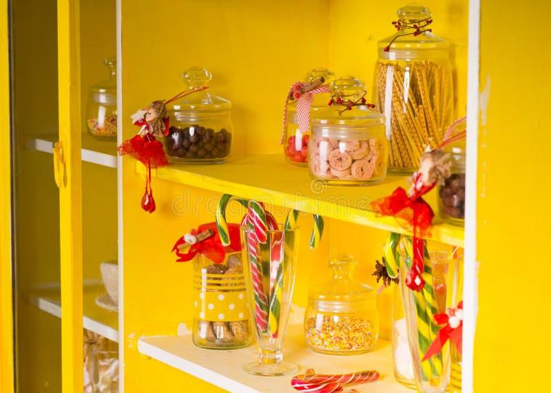 Caramelos en los tarros de cristal en los estantes amarillos fotografía de archivo libre de regalías