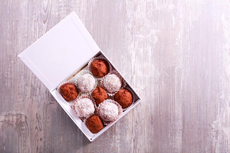 Caramelos hechos en casa de la trufa y de la fruta en una caja fotos de archivo