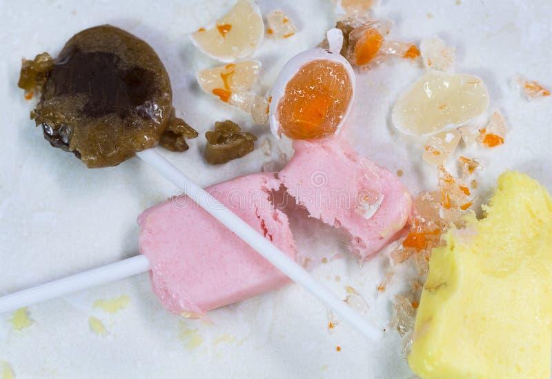 Caramelos quebrados con el azúcar en el fondo blanco fotos de archivo