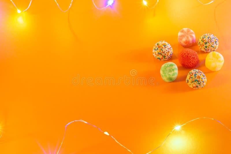 Caramelos y caramelos coloridos en un fondo anaranjado Pequeñas luces llevadas de colores Concepto horizontal de la celebración d fotografía de archivo