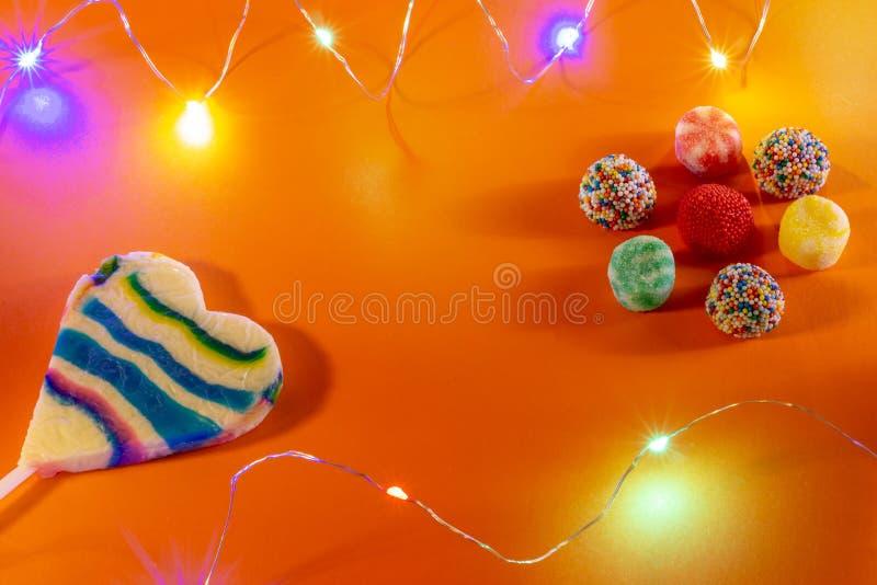 Caramelos y caramelos coloridos en un fondo anaranjado Pequeñas luces llevadas de colores Concepto horizontal de la celebración d fotos de archivo libres de regalías