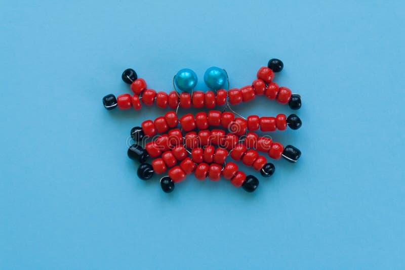 Caranguejo feito dos grânulos, os ofícios das crianças em um fundo azul fotos de stock royalty free