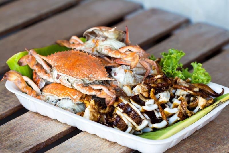 Caranguejos e calamar grelhados na bandeja da espuma imagem de stock