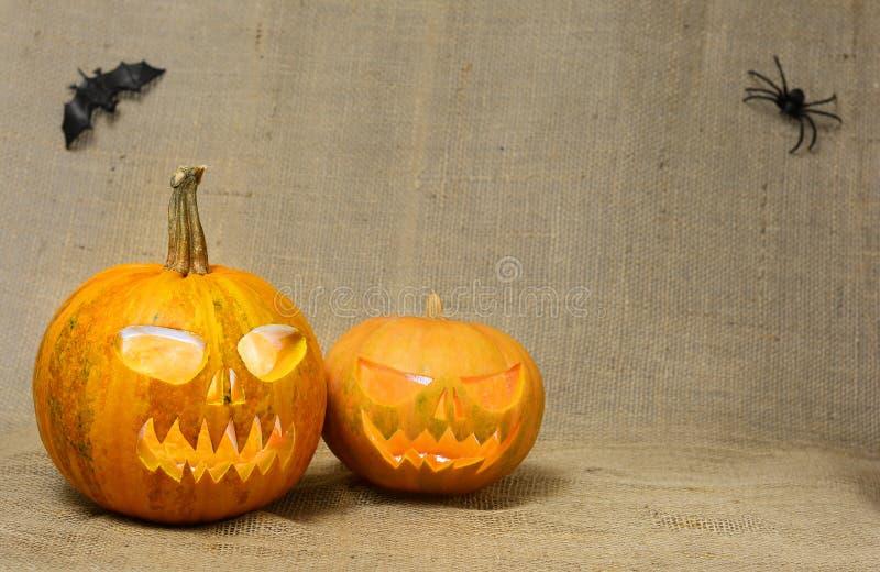 Caras asustadizas de las calabazas que brillan intensamente Calabazas asustadizas de Halloween en un fondo de la arpillera foto de archivo libre de regalías