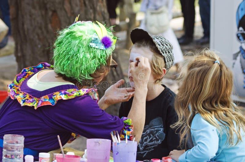 Caras coloridas chamativos da pintura da mulher das crianças no carnaval fotografia de stock