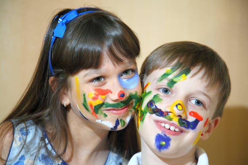 Caras das pinturas das crianças com cores fotos de stock