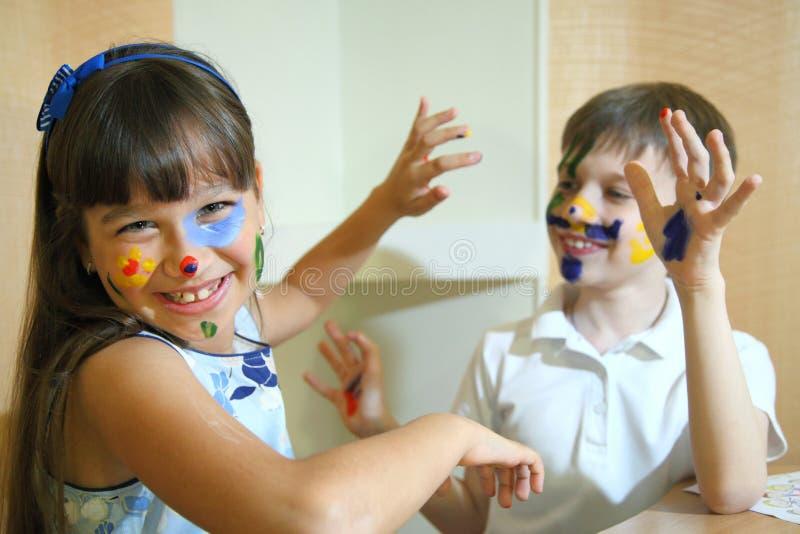 Caras das pinturas das crianças com cores imagem de stock