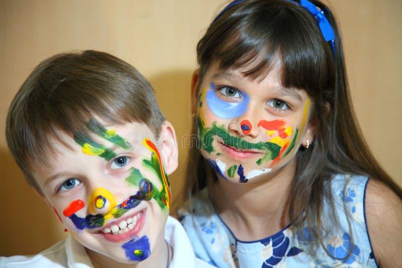 Caras das pinturas das crianças com cores foto de stock