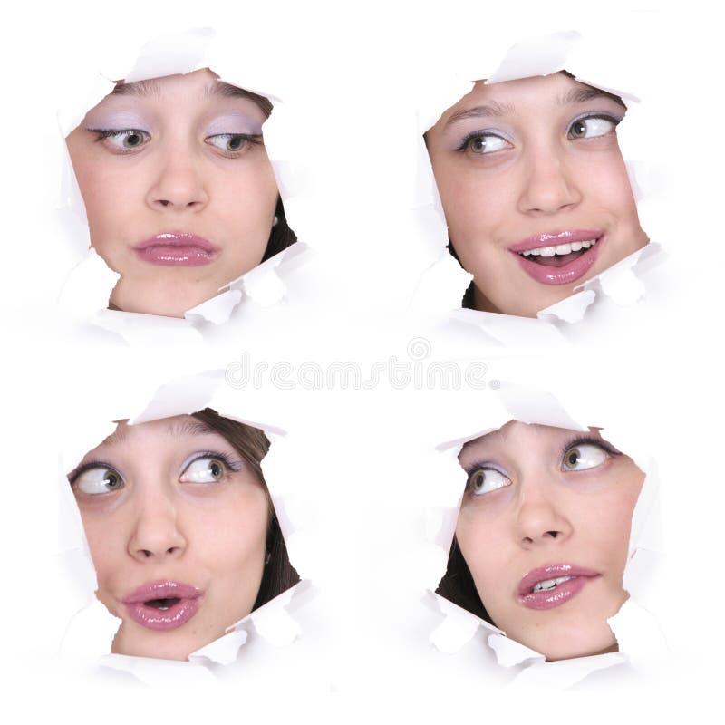Caras de la muchacha en un agujero de papel fotografía de archivo libre de regalías