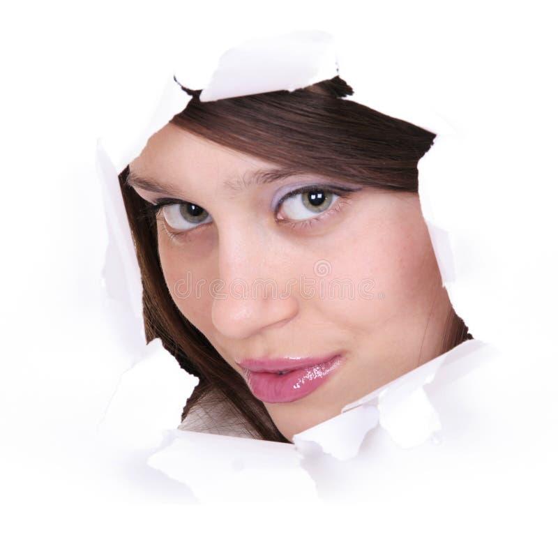 Caras de la muchacha en un agujero de papel imágenes de archivo libres de regalías