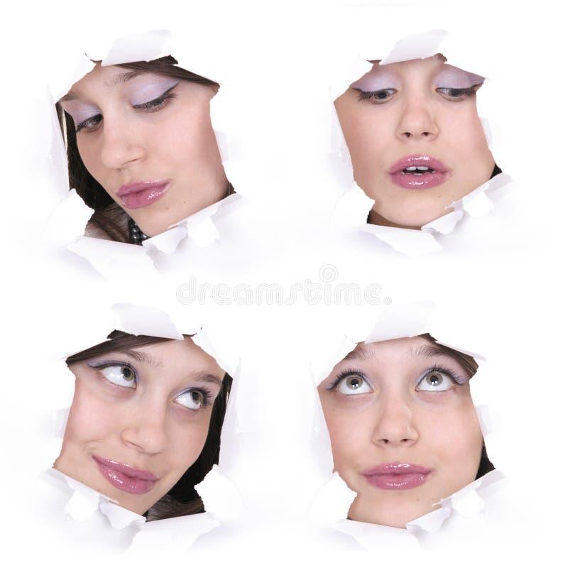Caras de la muchacha en un agujero de papel imagen de archivo libre de regalías