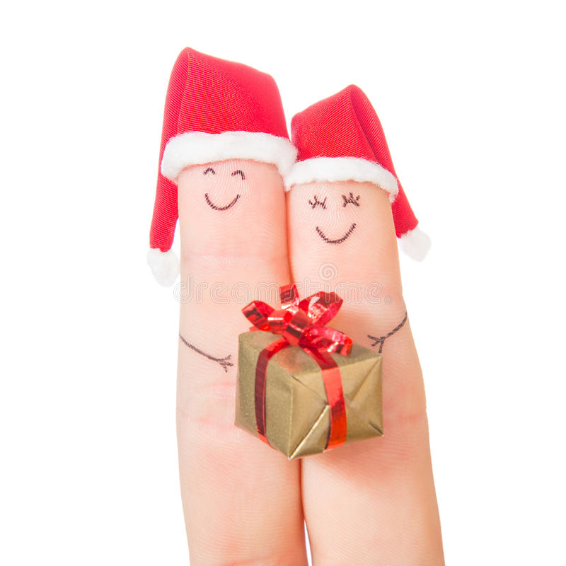 Caras de los fingeres en los sombreros de Papá Noel con la caja de regalo imagen de archivo